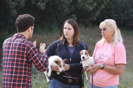 Director Zachary Sluser works with Dog Trainers Sarah and Candy (holding Harly and JJ, respectively)